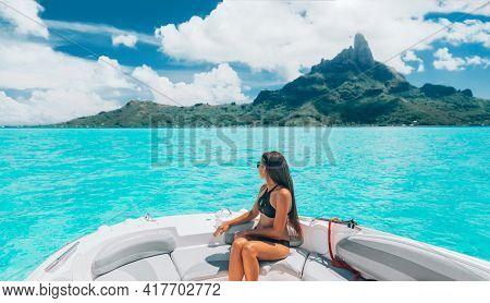 Luxury yacht travel woman enjoying ride on high end speed boat on summer vacation. Elegant black bikini, long hair and sun tanned body. By famous Mount Otemanu, Bora Bora, French Polynesia, Tahiti