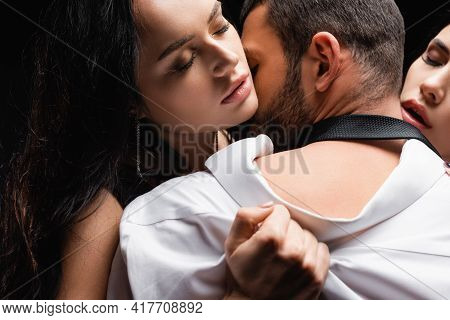 Passionate Women With Closed Eyes Undressing Man Isolated On Black.