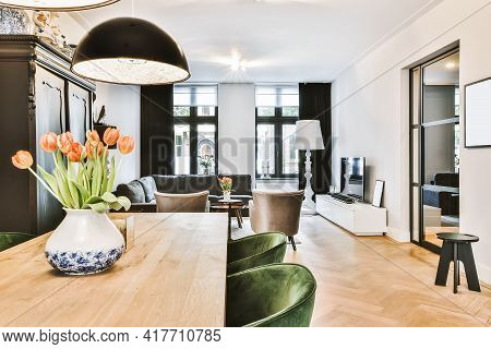 Interior Of Light Room With Stylish Dining And Lounge Areas In Modern House At Daytime