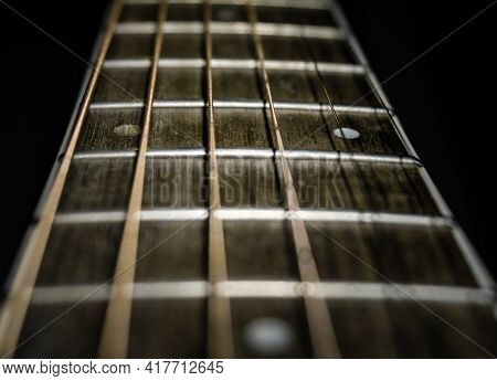 A Closeup Shot Of A Guitar Fretboard Using Shallow Depth Of Filed And Black Background.
