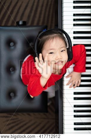 Vertical Image Of Asia Toddler Girl Look Up Toward Camera While Playing Piano With Small Smile, Expl