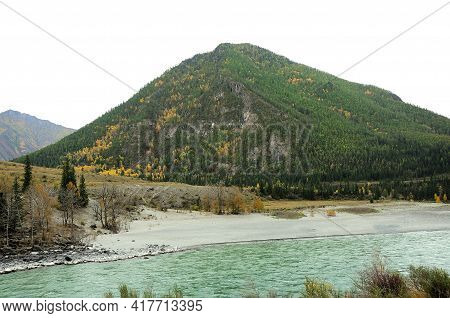 A High Mountain Covered With Coniferous Forest On The Banks Of A Beautiful Stormy River.