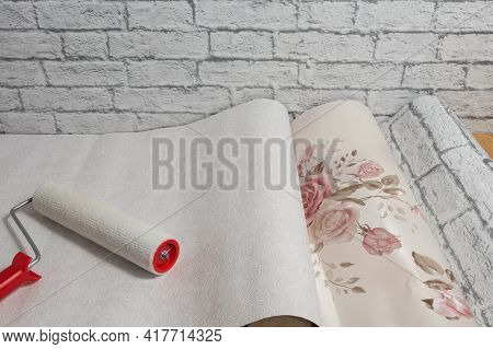 Rolls Of Wallpaper With A Pattern And A Roller Are Laid Out On The Floor And Prepared For Renovation