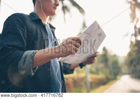 A Man With Backpack Hiking Read A Map And Him Walking On The Road In Forest. Backpack Travel Concept