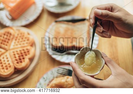 Hand Use Spoon To Scoop Pineapple Jam, Yellow Jam From Jam Cup. Dessert Concept.
