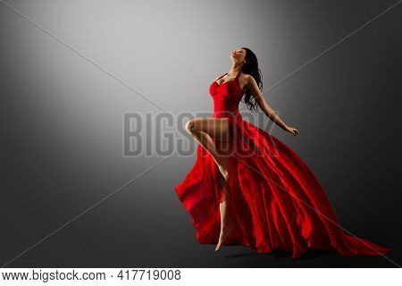 Dancer In Red Dress Jumping. Woman Ballerina Expressive Balance Dance Flying Fabric In Air. Fashion