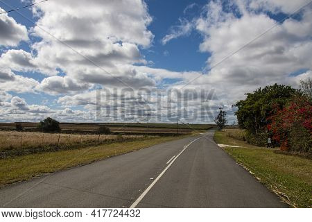 Rural Tarmac Country Road Bordered By Farm Land