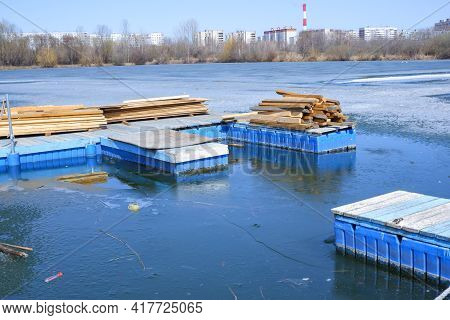 Stacked Wooden Planks On The Dock. The Lake Is Covered With Ice. For Construction And Finishing Work