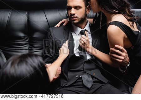 Sensual Women Seducing Young Businessman On Blurred Foreground Isolated On Black.
