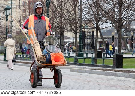 Moscow, Russia - April 2021: Worker Carries A Wheelbarrow With Repair Equipment In The Alexander Gar