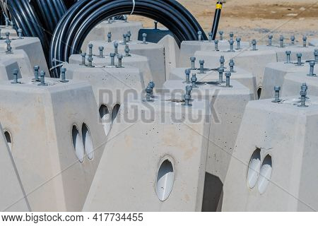 Concrete Bases For Lampposts At Construction Staging Area In Front Of Coils Of Black Pvc Pipe.