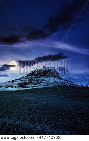 Castle On The Hill At Night. Composite Fantasy Landscape. Grassy Meadow In The Foreground. Rocky Pea