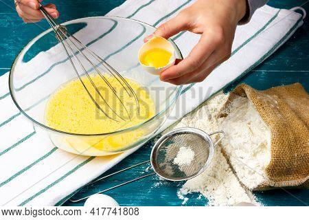 Female Hands Are Preparing Pancake Dough. The Girl Adds Egg Yolk To A Glass Bowl Of Dough. Dough Pre