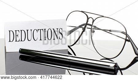 Text Deductions On White Sticker Paper On Light Background With Pen And Glasses. Business