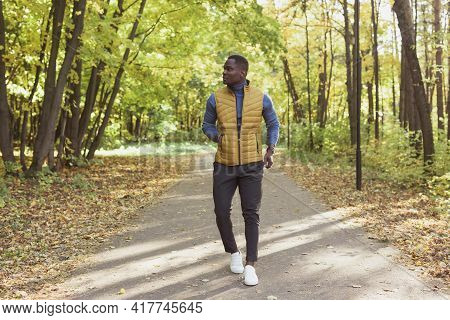 Cheerful African American Young Man In Stylish Clothes Walks In Autumn Park On Sunny Warm Autumn Day