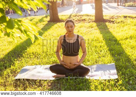 Cute Young Caucasian Pregnant Woman Is Meditating While Sitting On A Rug On The Lawn On A Sunny Summ