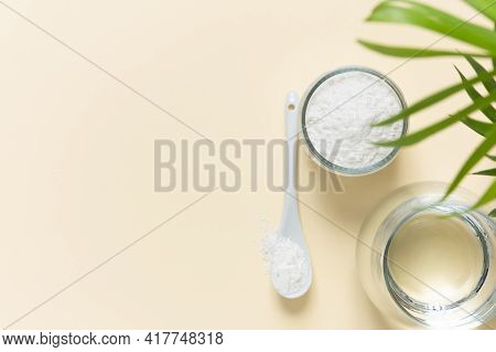 Collagen Powder And A Glass Of Water On A Beige Background With A Copy Space. Extra Protein Intake