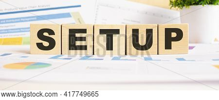 Setup Word On Wooden Cubes. The Background Is A Business Graphs. Finance Concept