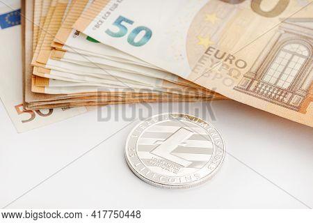Litecoin Coin And Euro Banknotes. Blockchain Money Versus Fiat Money Concept