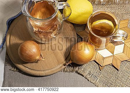View From Above. On A Round Board Lie An Onion, A Lemon, And A Jug With Onion Skins. Nearby Is A Cup