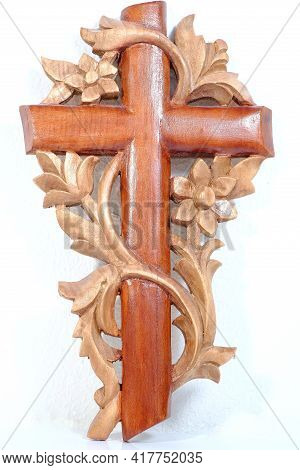 A Beautiful Handmade Wooden Cross On A White Background