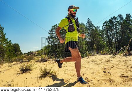 An Athlete Runs On A Sandy Area On A Hot Day. Running In The Desert. A Man In Shorts And A T-shirt R