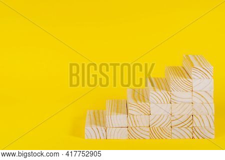 Wooden Blocks Forming Stairway On Yellow Background. Ladder Of Success, Business Investment Growth,
