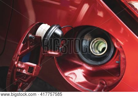 Fuel Tank Cap Hanging On The Fuel Tank Door Of A Red Car For Waiting Fill Up With Gasoline Or Diesel