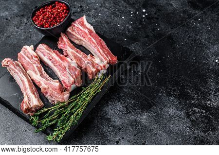 Raw Sliced Veal Spare Loin Ribs On A Marble Board. Black Background. Top View. Copy Space