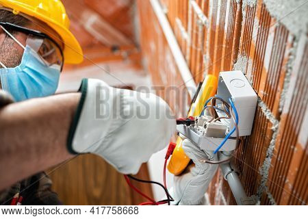 Electrician At Work With Face Protected By Surgical Mask To Prevent Coronavirus Infection. Covid-19