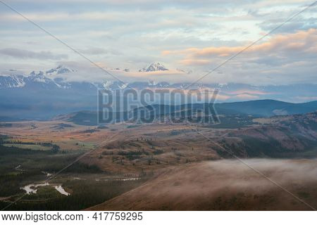 Scenic Alpine Landscape With Low Clouds In Vast Plateau With Mountain River And Forest On Background