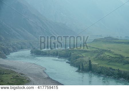 Beautiful Misty Mountain Landscape With Wide Mountain River. Dark Green Gloomy Scenery With Big Moun