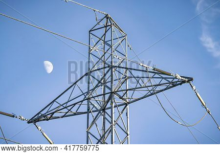 Detail Of Electricity Pylon With The Moon Against A Blue Sky, Depicting Uk National Grid And Electri