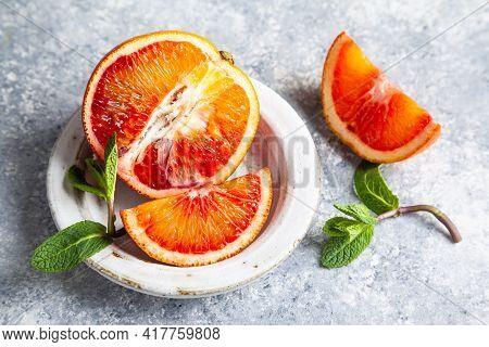 Sliced Sicilian Bloody Orange In Ceramic Plate On A Grey Background.