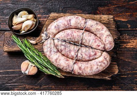 Raw Sausages From Pork And Beef Meat On The Wooden Cutting Board. Top View. Dark Wooden Background