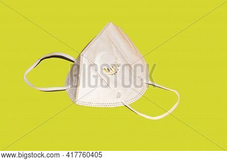 Respiratory Mask With Valve For Respiratory Protection On A Yellow Background. Recommended During Pe