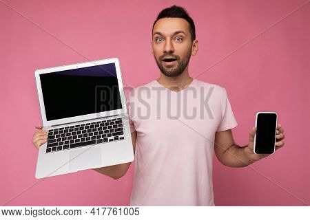 Handsome Amazed Man Holding Laptop Computer And Mobile Phone Looking At Camera In T-shirt On Isolate