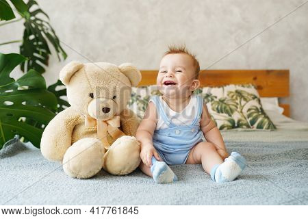 Adorable Baby Boy Sitting On The Bed And Laughs In White Sunny Bedroom With Toy Teddy Bear And Green