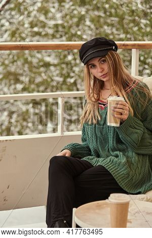 A Blonde Girl Is Sitting At A Table On The Veranda Against The Background Of A Winter Snow-covered P