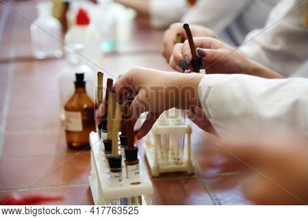 Girl Students Conducting Scientific Experiment In Chemistry Laboratory Classroom. Close Up Hand Stud