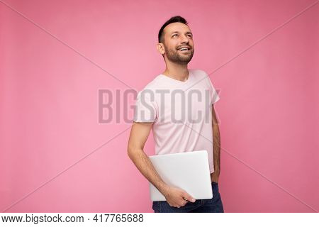 Handsome Happy Young Unshaven Man Holding Laptop Computer Looking Up In T-shirt On Isolated Pink Bac