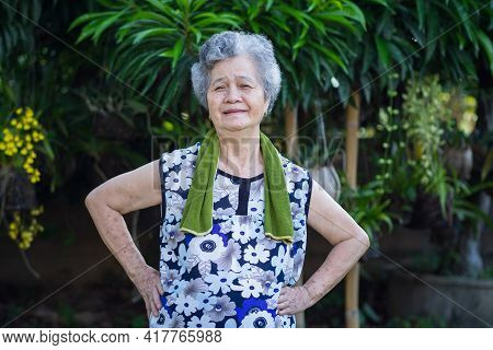 Portrait Of An Asian Senior Woman Wearing Casual Clothing Smiling And Exercises In Her Garden. Beaut