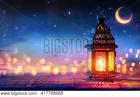 Muslim Holy Month Ramadan Kareem - Arabic Lantern With Burning Candle And Bokeh Glowing At Evening -