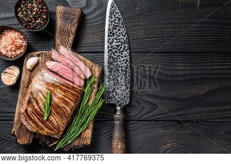 Bbq Grilled Flank Or Flap Beef Meat Steak On A Wooden Cutting Board. Black Wooden Background. Top Vi