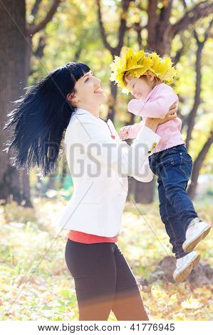 Beautiful Young Mother Holding Her Daughter In A Wreath Of Maple Leaves
