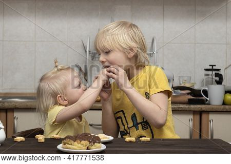 Blond Younger Sister Treats Her Brother To Sweets. Breakfast In The Kitchen. Siblings.