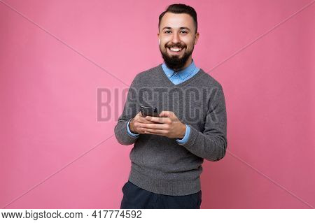 Positive Smiling Handsome Good Looking Brunet Bearded Young Man Wearing Grey Sweater And Blue Shirt