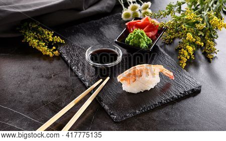 Traditional Japanese Dish - Nigiri Sushi prepared with Vinegar Rice and Shrimp. Black Slate Sushi Plate with chopstick and Soy Sauce Dip. Authentic Japanese Cuisine