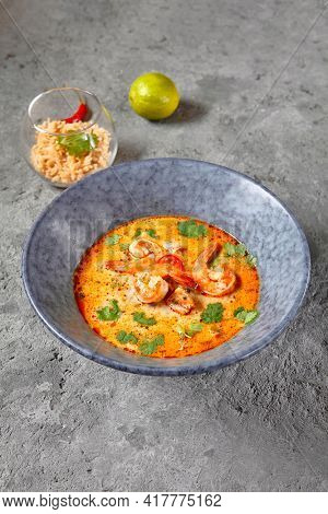 Tom Yum or Tom Yam Soup - Hot and Sour Thai Soup cooked with Shrimp. Thai Authentic Traditional Dinner. Soup in Blue Bowl on Dark Grey Table. Street Asian Food