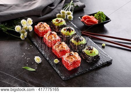 International maki sushi roll on black slate plate. Served with wooden chopstick, green wasabi and pickled ginger. Japanese set with maki sushi roll on dark stone background.